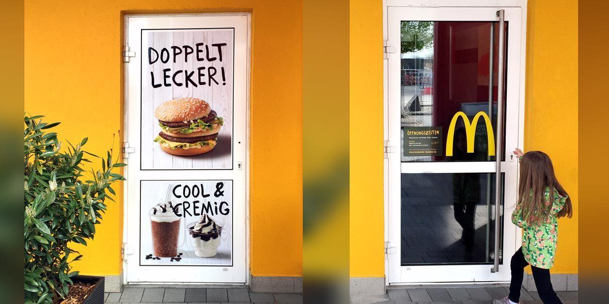 """Zwei Eingangstüren zum Burgerrestaurant mit der Beschriftung """"Doppelt Lecker!"""""""
